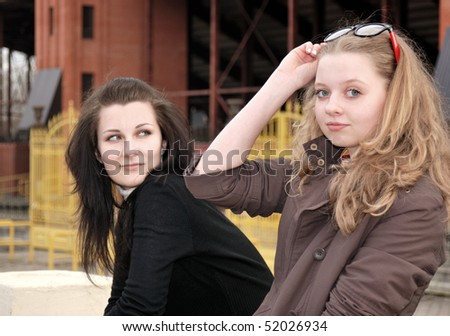 Two teenage girls hanging out near football stadium - stock photo