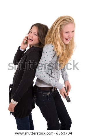 Two teenage girls having a laugh while on their phone