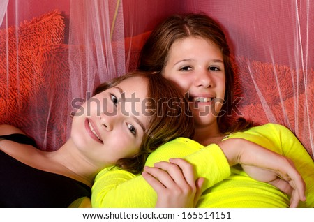 Two teenage girls having fun on the bed. - stock photo