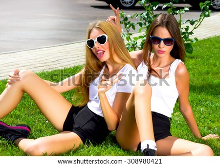 Two teenage girls having fun outdoors.Friends students. Girls students  look at the camera  and going crazy while sitting on grass near the campus of the University at the break. Positive and happy. - stock photo