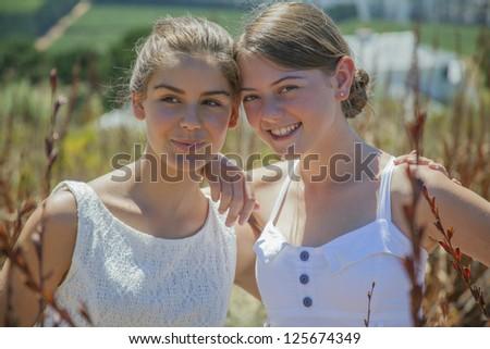 Two teenage girls having lots of fun outside - stock photo