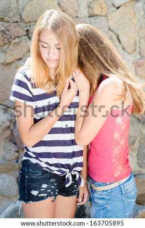 Two teenage girls hug for comfort on summer day at stone wall - stock photo