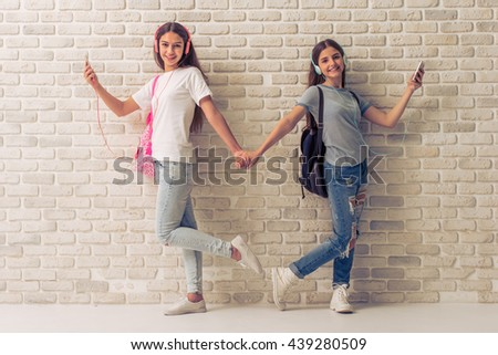 Two teenage girls in headphones are listening to music using smartphones, holding hands and smiling, standing against white brick wall - stock photo