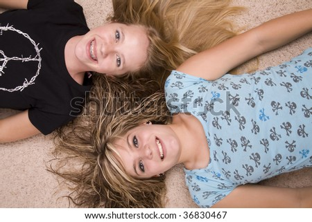 Two teenage girls laying with heads together on the floor.