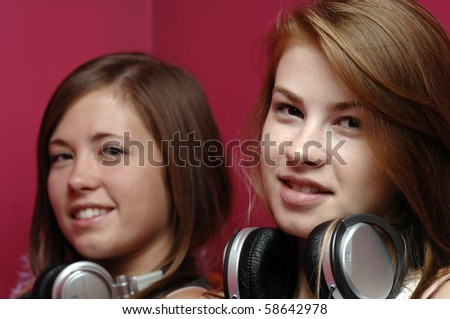 Two teenage girls listen some tunes using headset in their room. - stock photo