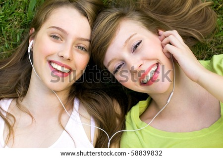Two teenage girls listening to MP3 player - stock photo