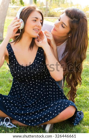 Two teenage girls listening to music in the park