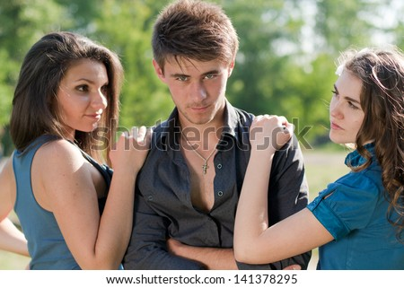 Two teenage girls looking jealousy on one guy outdoor closeup on the bright sunny day & green summer outdoors background - stock photo