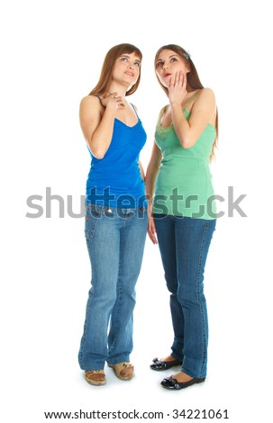 Two teenage girls looking up. Isolated on white background