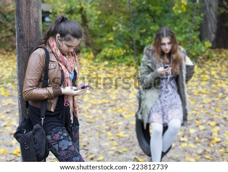 two teenage girls on a playground looking at their phones - stock photo