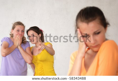 Two teenage girls pointing at their friend. Uniform background - stock photo