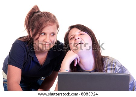 Two teenage girls reacting to a laptop computer screen with blue hi-lites from the screen illumination - stock photo