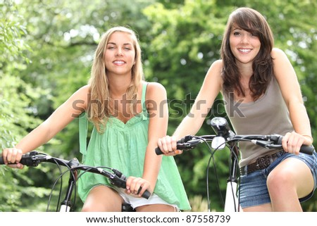 Two teenage girls riding bikes in the countryside - stock photo