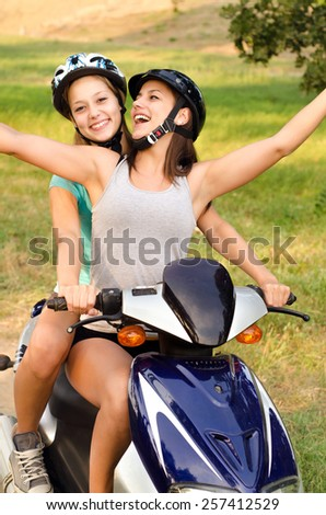 Two teenage girls riding motorcycle in the nature on sunny summer day. - stock photo