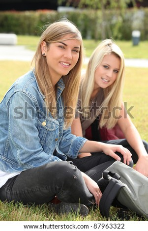 Two teenage girls sitting in a park - stock photo
