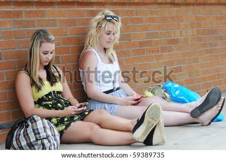 Two teenage girls sitting next to a brick wall texting on their smart mobile cellphones. - stock photo