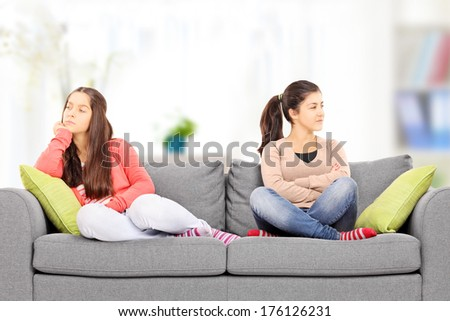Two teenage girls sitting on sofa, at home, angry with each other - stock photo