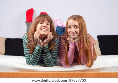 Two teenage girls smiling while lying on the bed. - stock photo