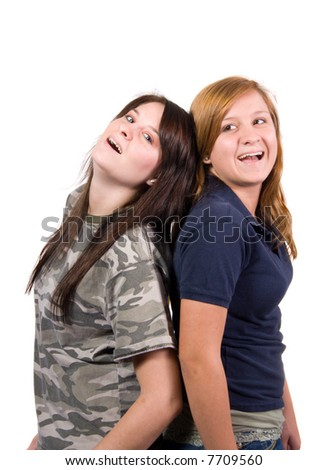 Two teenage girls standing back to back smiling shot over white - stock photo