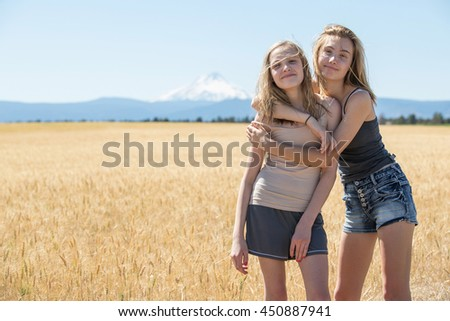 Two teenage girls standing in a wheat field - stock photo