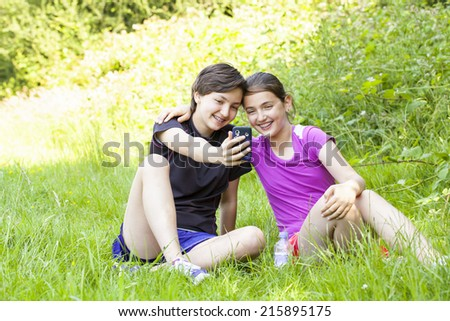 Two teenage girls taking photos of themselves with the phone