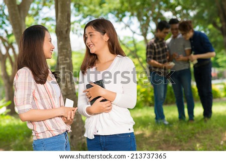 Two teenage girls talking in the park on the background of their male classmates using cellphone - stock photo