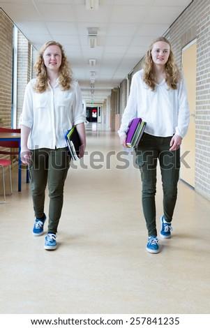 Two teenage girls walking in long school corridor carrying text books - stock photo