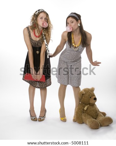 Two teenage girls wearing pretty dresses blowing bubble gum. - stock photo