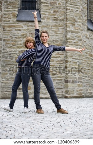 Two teenage girls wearing the same dress and posing together - stock photo