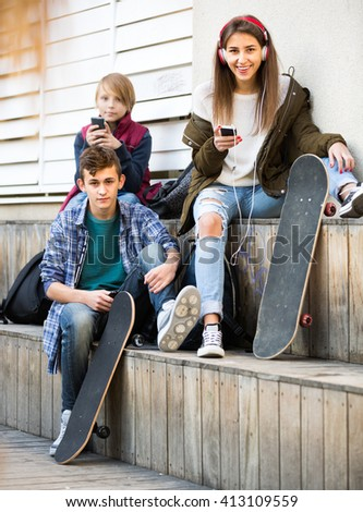 Two teenage males and their girlfriend busy with mobile phones outdoor