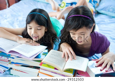 Two teenage sisters enjoying their reading at home.