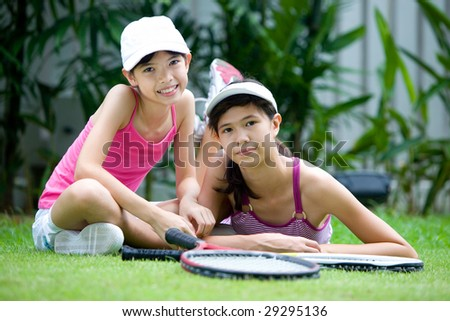 Two teenage sisters in tennis outfit, with rackets, outdoors - stock photo