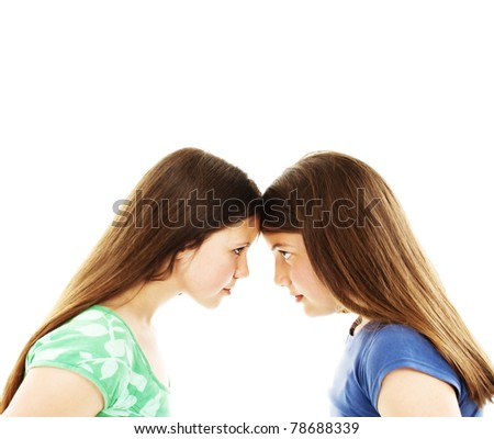 Two teenage sisters staring at each other isolated on white - stock photo