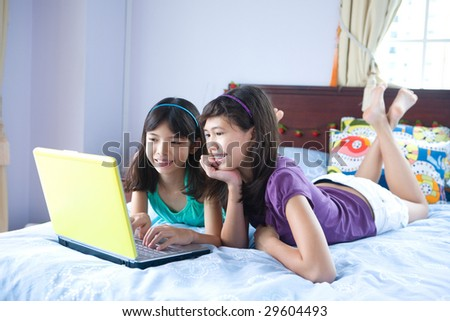 Two teenage sisters using personal computer at home
