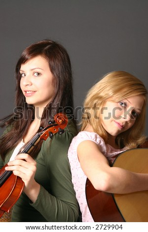 Two teenage sisters with violin and guitar against dark background