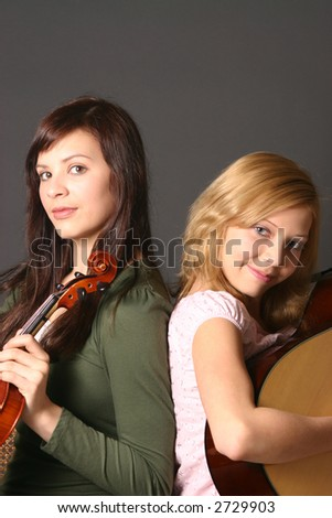 Two teenage sisters with violin and guitar against dark fiddle background
