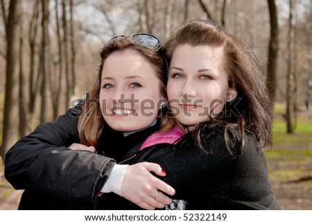 Two teenage smiling girls gives hugs each other in the park - stock photo