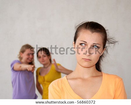 Two teenage smiling girls pointing at their friend. - stock photo