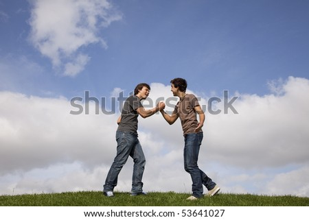 two teenager doing a special handshake - stock photo