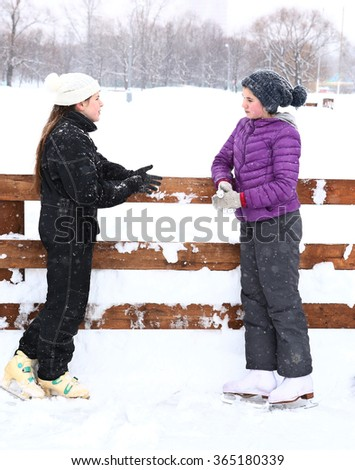 two teenager girl in knitted woolen hat and down overall and jacket ice skates full length body photo on the skating ring talk  smile on the snowy white background - stock photo
