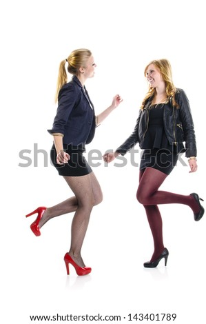 Two teenager girls having a party an dacing together isolated against white background. - stock photo