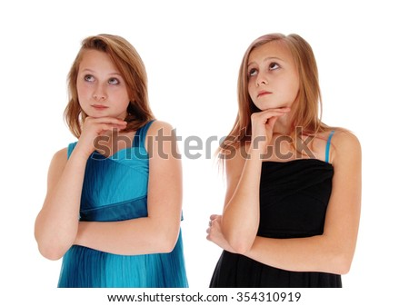 Two teenager girls in a black and blue dress with there hands under therechin, looking up, isolated foe white background. - stock photo