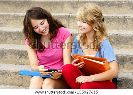 Two teenager girls laughing at texto or internet on their cell phone or mobile - stock photo