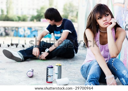 Two teenagers apart, breaking up, with graffiti background - stock photo