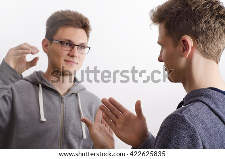 Two teenagers communicating with sign language, selective focus on face of the kid to the right. - stock photo