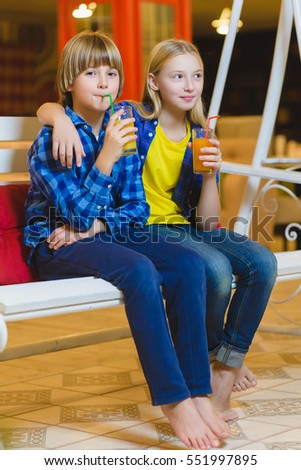 two teenagers or happy kids - boy and girl drinking juice in cafe
