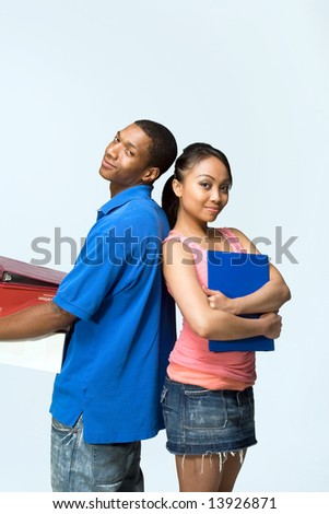 Two teenagers standing back to back holding notebooks are smiling. Vertically framed photograph - stock photo