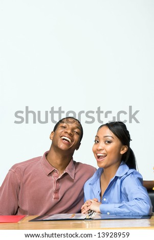 Two Teens are are seated at a desk  laughing, and smiling. There are  folders and paper on the desk. Vertically framed photograph - stock photo