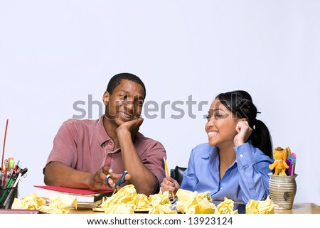 Two Teens are are seated at a desk looking at each other. There are  folders, pens, pencils, and crumpled paper on the desk. Horizontally framed photograph - stock photo