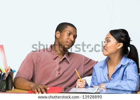 Two Teens are are seated at a desk taking notes and smiling at each other. There are pencils, folders, and paper on the desk. Horizontally framed photograph - stock photo